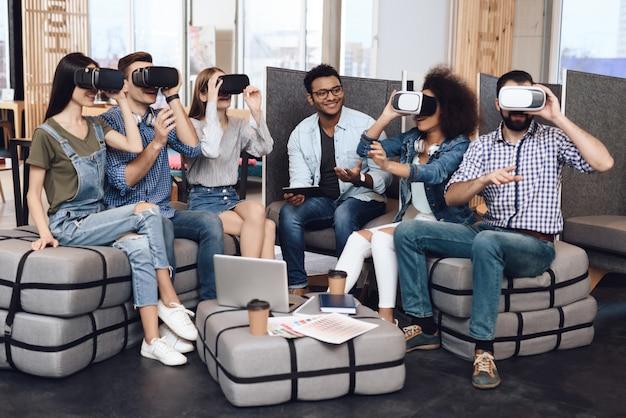 若いデザイナーのグループがバーチャルリアリティ眼鏡を見ています。