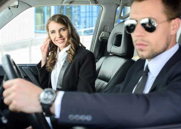 ビジネスマンやビジネスの女性が車の中で旅行します。