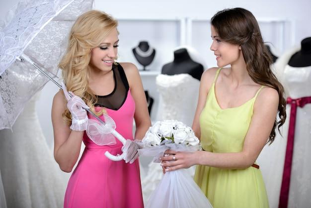 女の子は別の女の子に結婚式のための美しい花束を見せる。