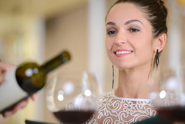 ワインのグラスを待っている若い上品な女性。