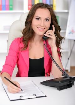 自信を持って若いビジネス女性が電話で話しています。