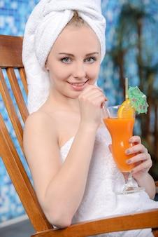 プールサイドでジュースを持つかなり笑顔の女性のクローズアップ。