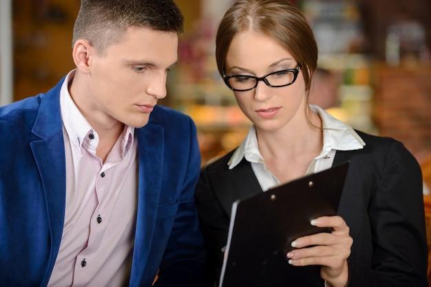 ビジネスマンやビジネスの女性がカフェで会議を行っています。