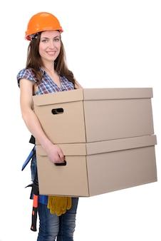 建設ヘルメットの少女は箱を抱えています。