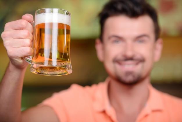 陽気な男がバーでビールを飲みます。