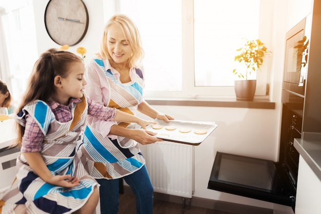 高齢の女性は、自家製のクッキーを調理する女の子を教えています。
