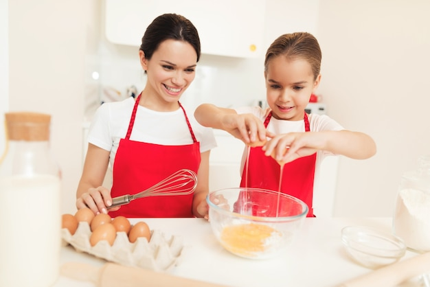 赤いエプロンの女性と少女がクッキーとマフィンを焼く。