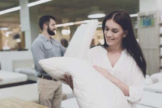 Пара в большом магазине выбирает подушки.