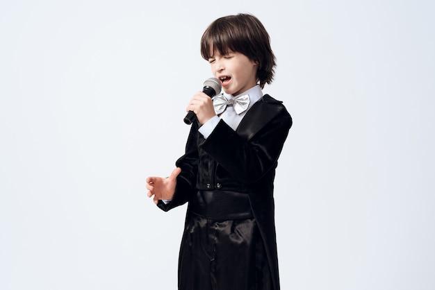 小さな男の子は歌手の職業を学びます。
