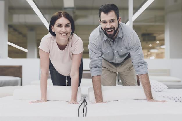 大きな店のカップルは、購入する前にマットレスを検査します。