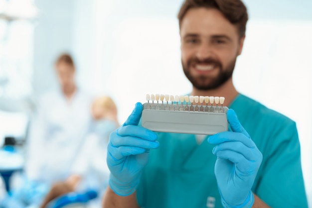 歯医者は歯のカラースケールでポーズをとっています。