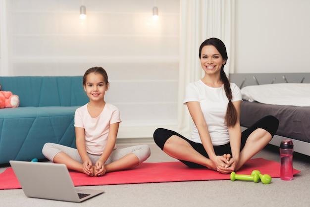 Мама и дочка делают гимнастику на коврике дома.