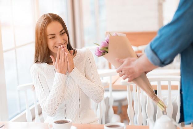 Сюрприз помолвка в кафе мужчина дарит цветы.