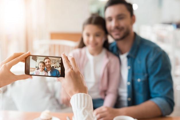 ママはスマートフォンで家族の写真を撮ります。