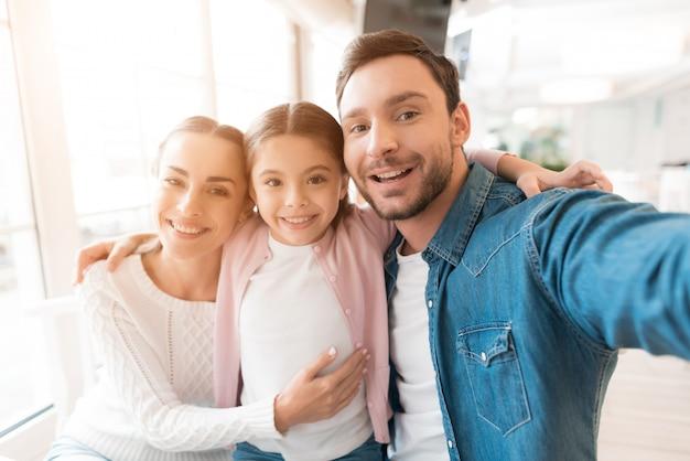 お父さんはスマートフォンで家族の写真を撮ります。