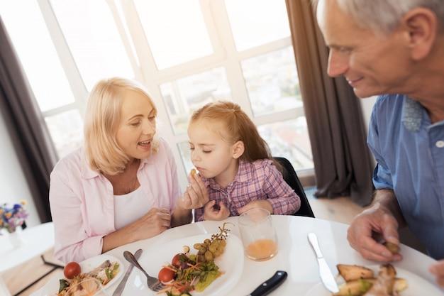 祖母はテーブルに座り、孫娘に餌をやる。