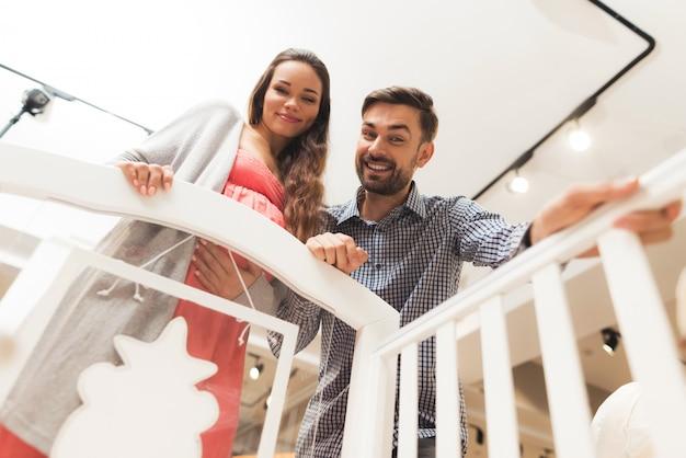 Беременная женщина и мужчина выбирают детскую кроватку.