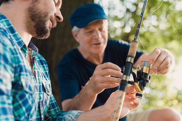 川でひげを生やした息子釣りと老父。