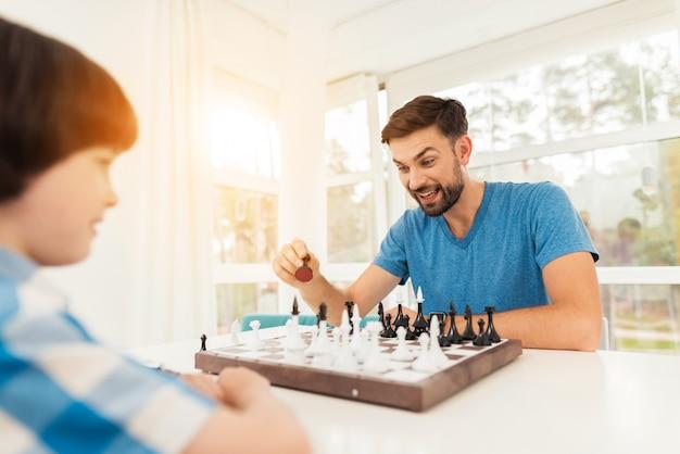 Отец и сын играют в шахматы у себя дома.