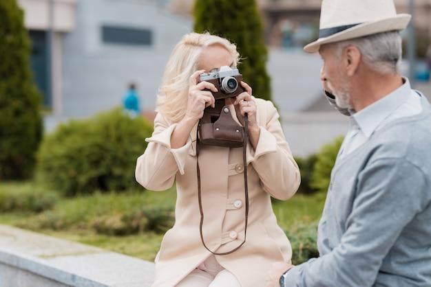 女性は、ビンテージフィルムカメラで老人の写真を撮る。