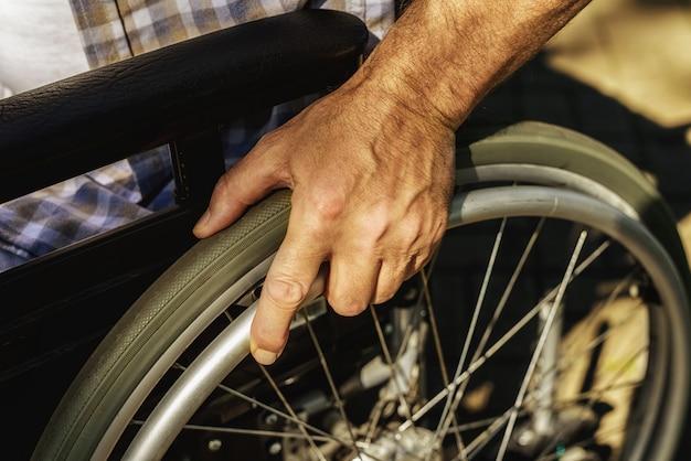 老人の手は車輪の上にあります。障害者支援。