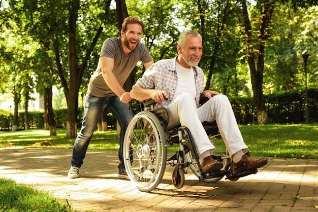 息子と老人は楽しい時を過します。公園を歩いている家族。