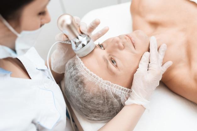 医者は男性の皮膚を光脱毛器で治療します。
