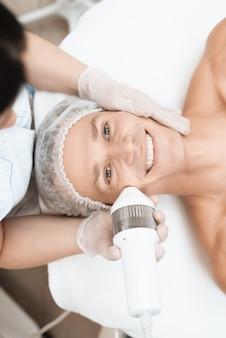 医者は、現代の光脱毛器で男性の皮膚を治療します。