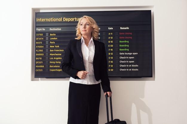 スーツを着た女性が空港に立っています。