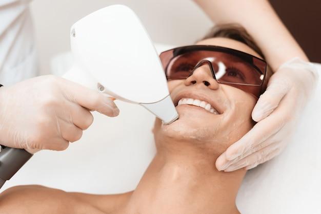 医師は現代のレーザー脱毛器で男性の顔を治療します