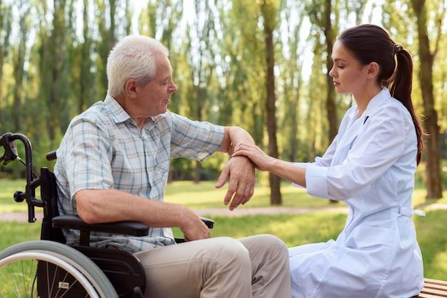介護士が老人の肘を調べる