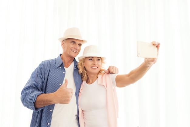 Пожилая женщина и пожилой мужчина в шляпах, делающих селфи.