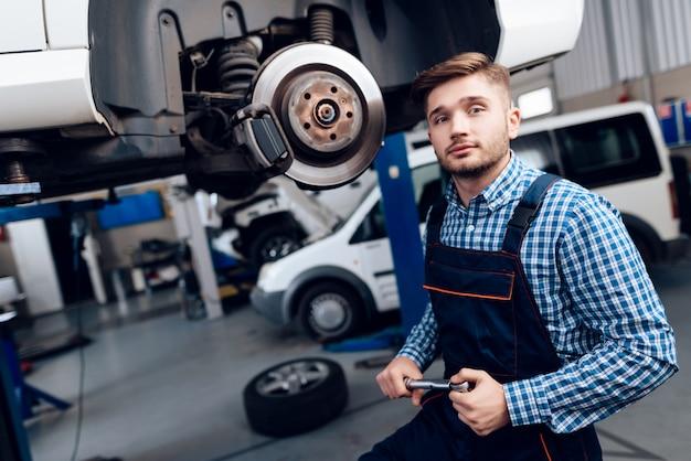 若い自動車整備士がガレージの自動車ハブを修理します。