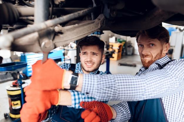 若いメカニックがガレージの自動車ハブを修理します。