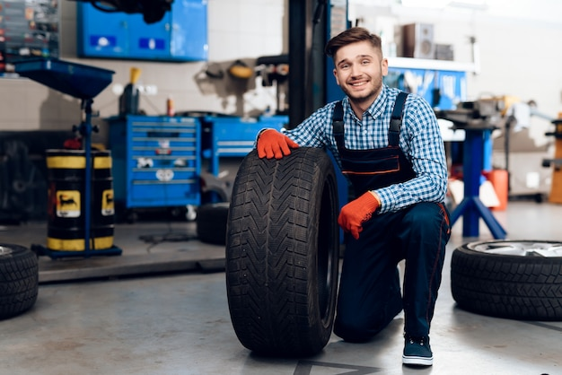 Молодой улыбающийся механик держит автомобильную шину на станции технического обслуживания.