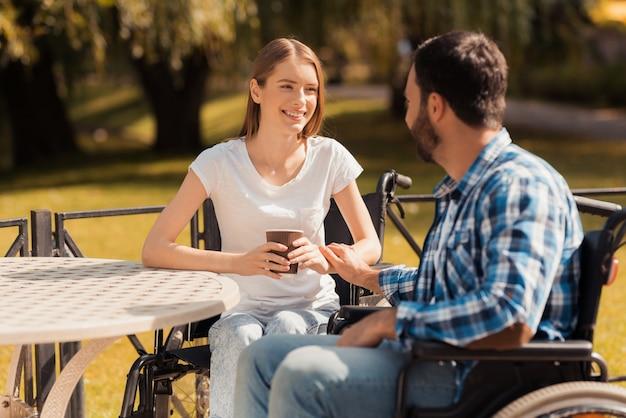 Пара инвалидов пьют кофе.
