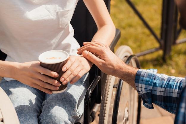 Болезнь женщина держит в руках стакан с кофе.