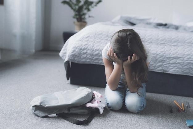 寝室の床に座って泣いている悲しい少女