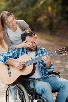 Мужчина на инвалидной коляске играет на гитаре в парке.