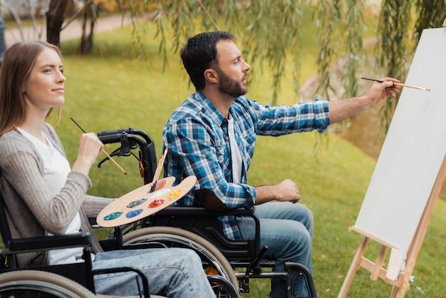車椅子の病人を持つ男女が一緒に描きます。