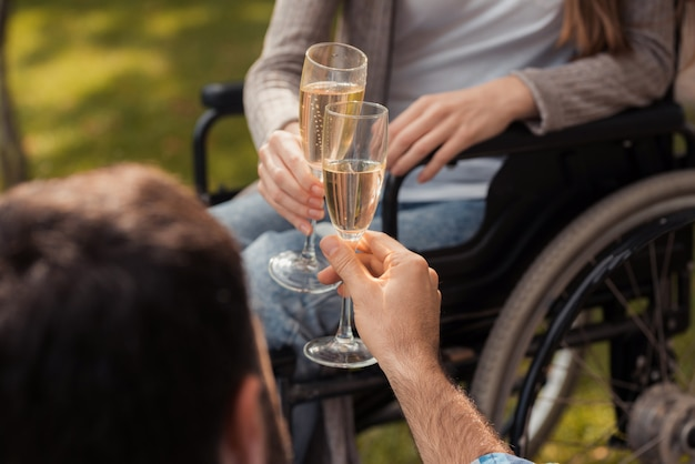 Закройте женщина в инвалидной коляске в парке с мужчиной.