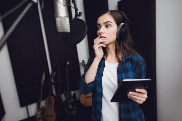 Девушка в студии звукозаписи в наушниках.