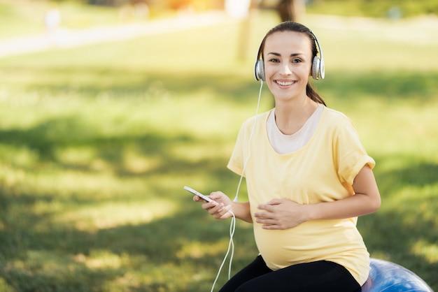 女性は公園に座って、音楽を聴いています。