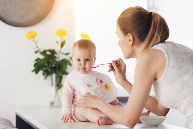 Женщина кормит ребенка ложкой.