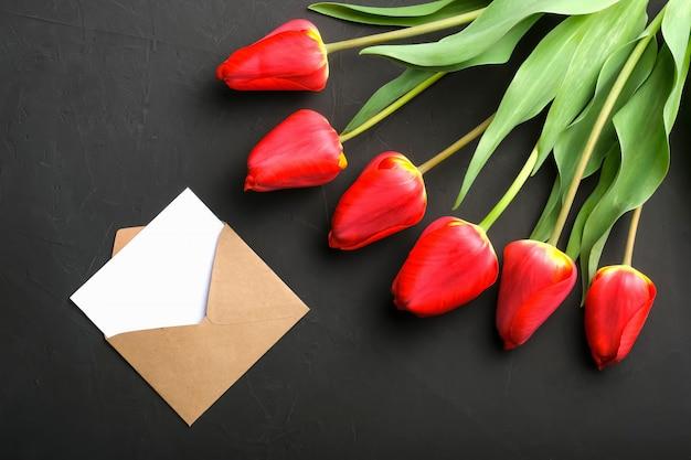 新鮮な赤いチューリップの花束とグリーティングカードクラフト封筒のモックアップ