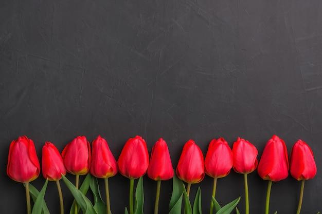 テキストのコピースペースを持つ行の赤いチューリップの花束。