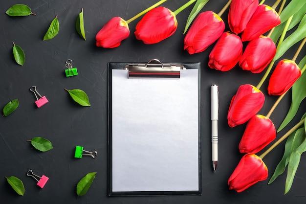 Вид сверху макет букета красных тюльпанов и зеленых листьев с буфером обмена и ручкой