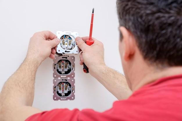 Электрик рука держит гнездо в процессе установки с помощью отвертки