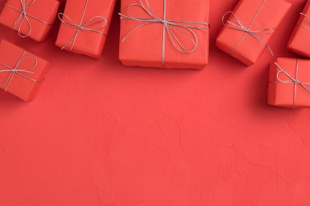 赤いクラフト用紙の背景に包まれたプレゼントの行