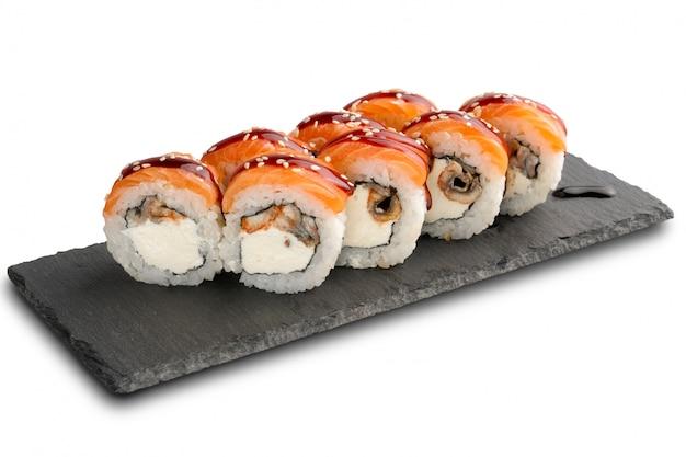 分離された黒いスレートまたは石の頁岩の表面にウナギとサーモンとクリームチーズの巻き寿司